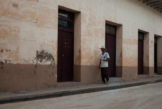 Beige-braune Hausfassade, vor der ein Mann entlang geht.