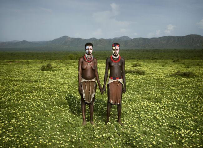 Zwei Menschen in Stammestracht auf einer Wiese