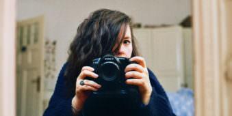 Selbstporträt einer Frau im Spiegel mit Kamera
