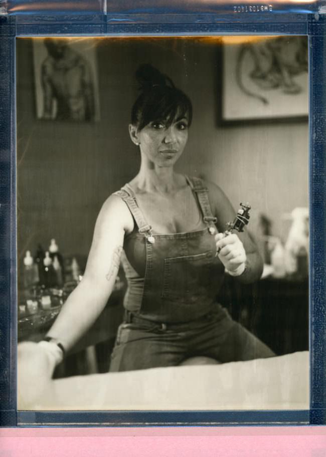 Portrait einer sitzenden Frau mit Tätowiernadel in der Hand