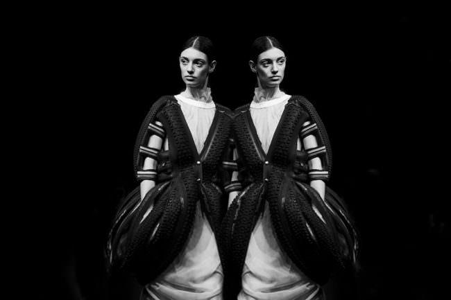 Eine Frau in einem schönen Kleid entspringt ihrem Spiegelbild.