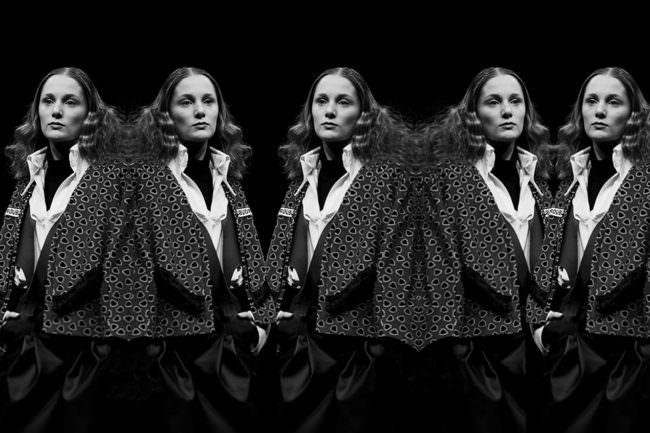 Eine Frau spiegelt sich mehrfach selbst auf schwarzem Hintergrund.