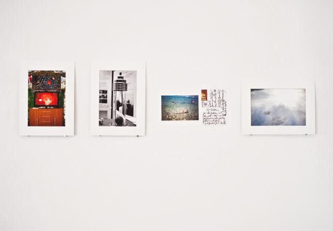Ausstellungswand mit Fotografien und Postkarte.