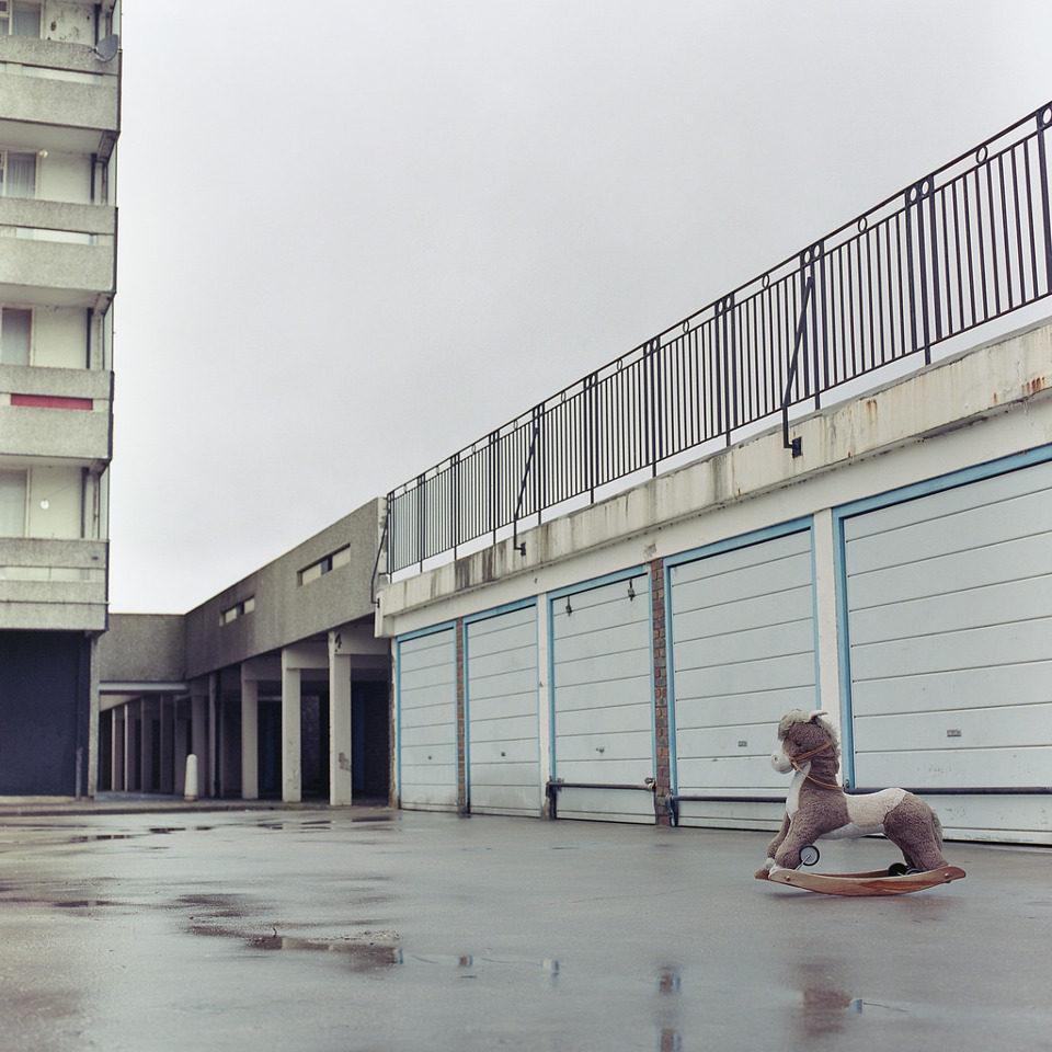 Ein Schaukelpferchen steht vor einer Garagenwand.