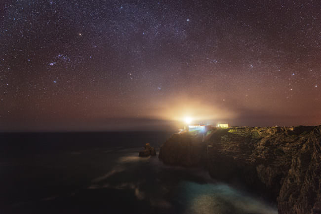 Ein Leuchtturm bei Nacht auf einem Felsen