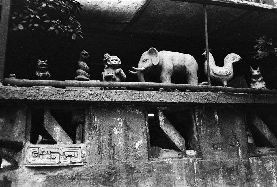 Auf einem Zaun aufgereihte Tierfiguren.