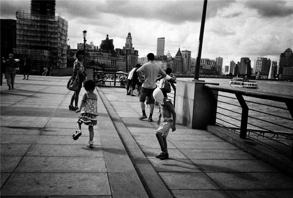 Spielende Kinder und weitere Passanten an einer Küstenstraße in der Stadt.