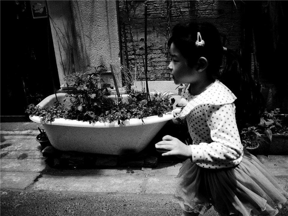 Ein Mädchen läuft in einer Straße vor einer bepflanzten Badewanne entlang.