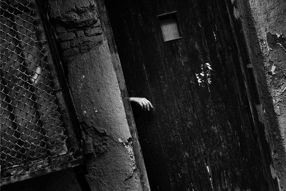 Eine Hand ragt aus einem Türspalt.