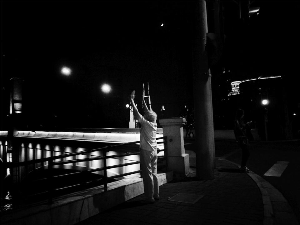 Ein Mensch nachts in der Stadt, streckt seine Arme zum Himmel aus.