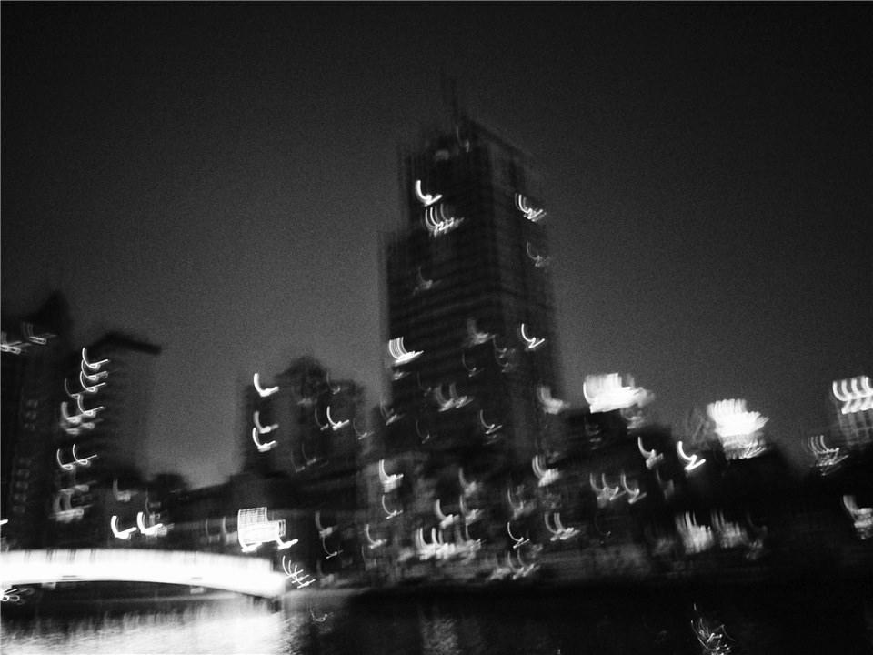 Verwackelte Aufnahme von Hochhäusern in der Nacht.