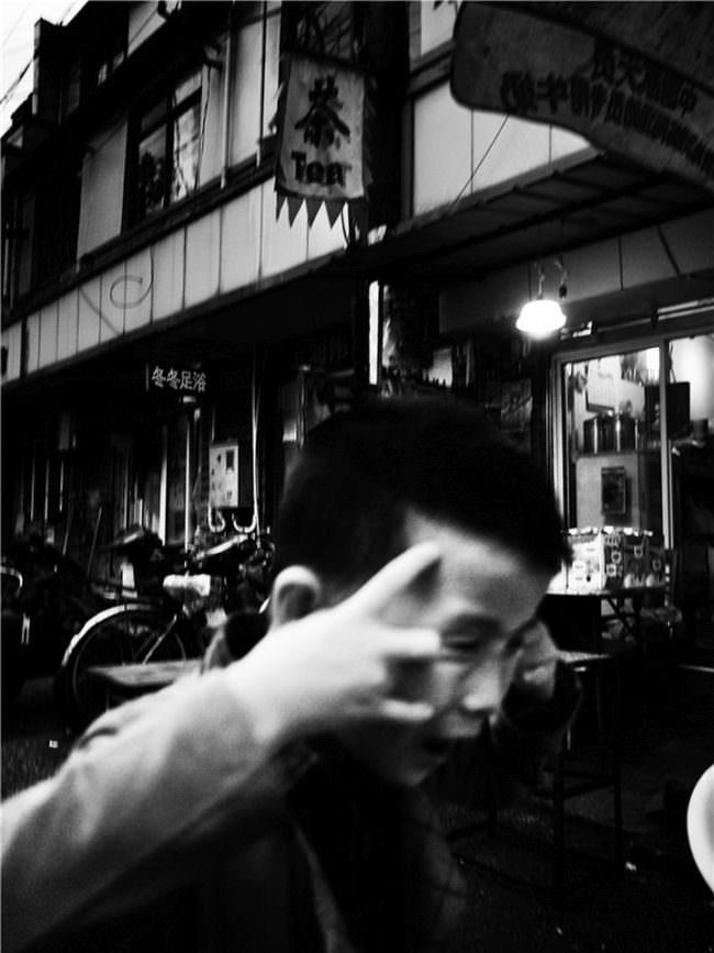 Ein Mann fasst sich auf einer Einkaufsstraße mit beiden Händen an den Kopf.