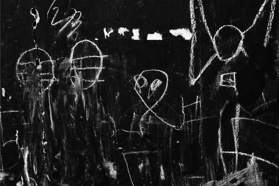 Kreidegekritzel auf einer dunklen Wand.