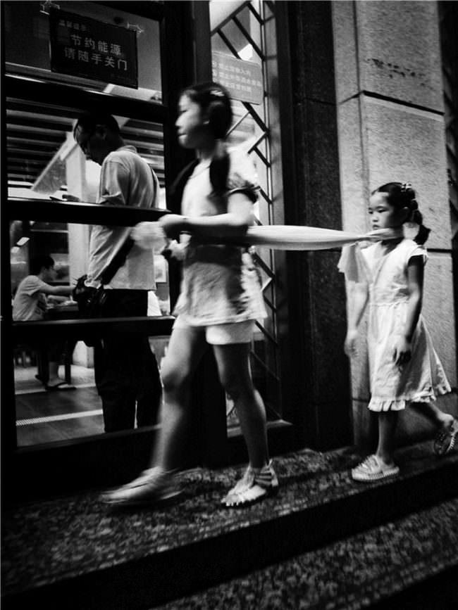 Ein Mädchen führt ein weiteres an einer um den Hals gebundenen Leine eine Straße entlang.