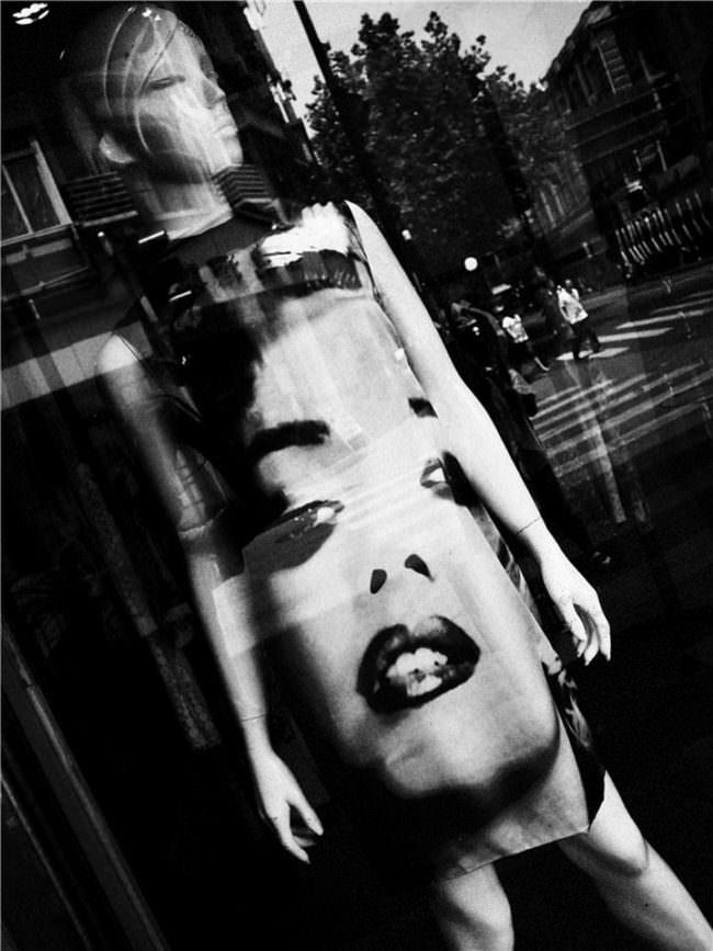 Schaufensterpuppe mit einem Kleid mit einem großen Gesicht bedruckt.