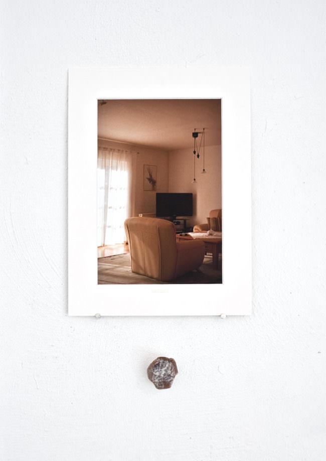 Foto eines Wohnzimmers hängt über einem Stein an der Wand.