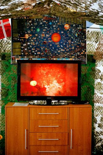 Eine Planetenkarte hängt über einem Fernseher.