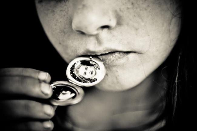 Bilder in einem Medaillon, das sich ein Mädchen an die Lippen hält.