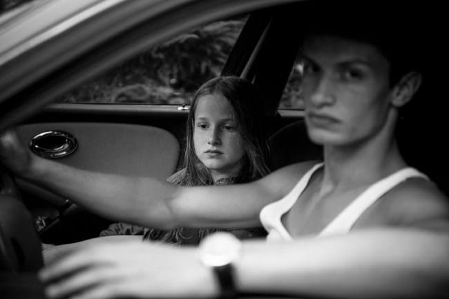 Ein Mädchen und ein älterer Junge sitzen in einem Auto.