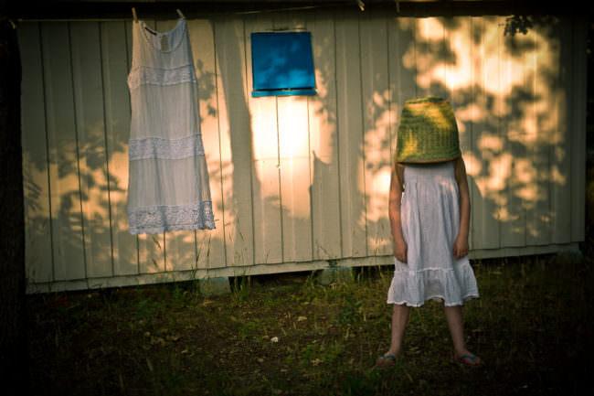 Ein Mädchen steht im Garten und hat einen Korb auf dem Kopf.
