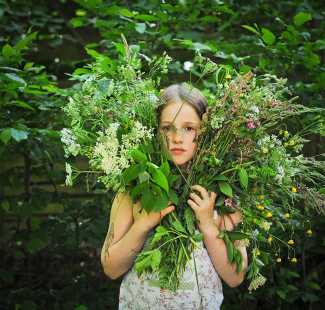 Ein Mädchen hinter einem Wildblumenstrauß.