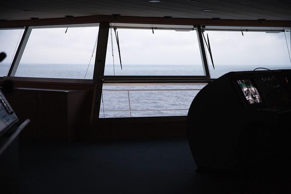Blick auf das Meer durch ein Schiffsfenster.