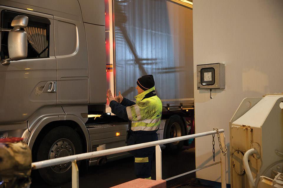Mann in Warnkleidung werkelt an einem LKW.