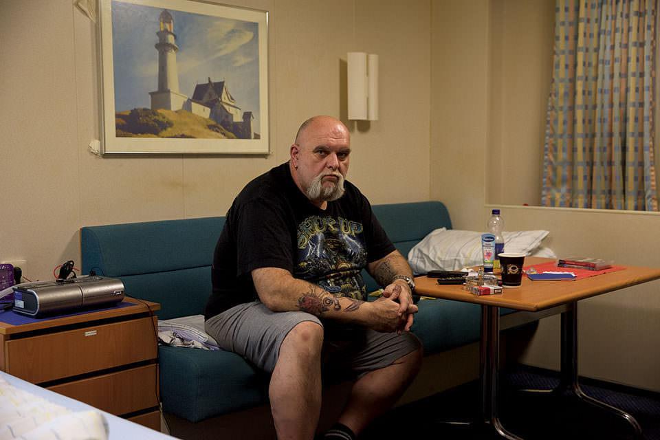 Mann bärtig und tätowiert sitzend im Innenraum, Leuchtturmbild an der Wand.