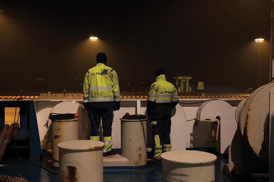 Deckarbeiter von hinten an Bord in Schutzkleidung im Dunkeln.