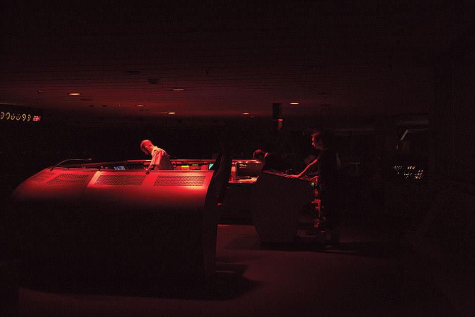 Innenraum in rot beleuchtet, Mann an Geräten.