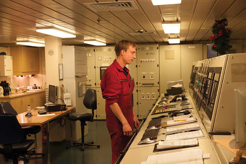 Mann im roten Overall vor Gerätetisch im Innenraum.