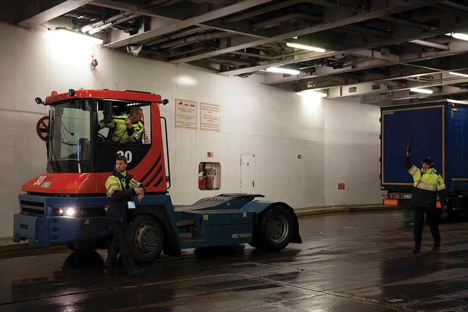 Kleiner LKW in einem Schiffsinnenraum.