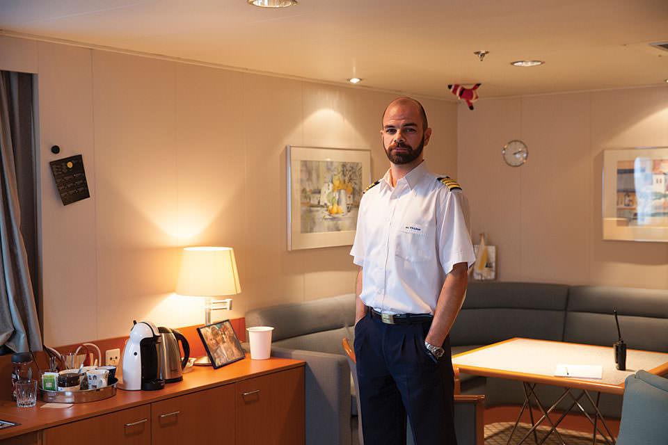 Portrait stehend von einem Mann in Uniform im Innenraum.
