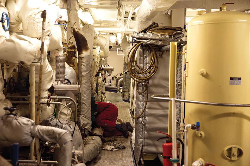 Schläuche und Maschinen sowie Kabel in einem Maschinenraum.