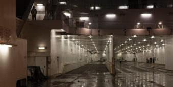Deckansicht eines Schiffes beleuchtet bei Nacht.