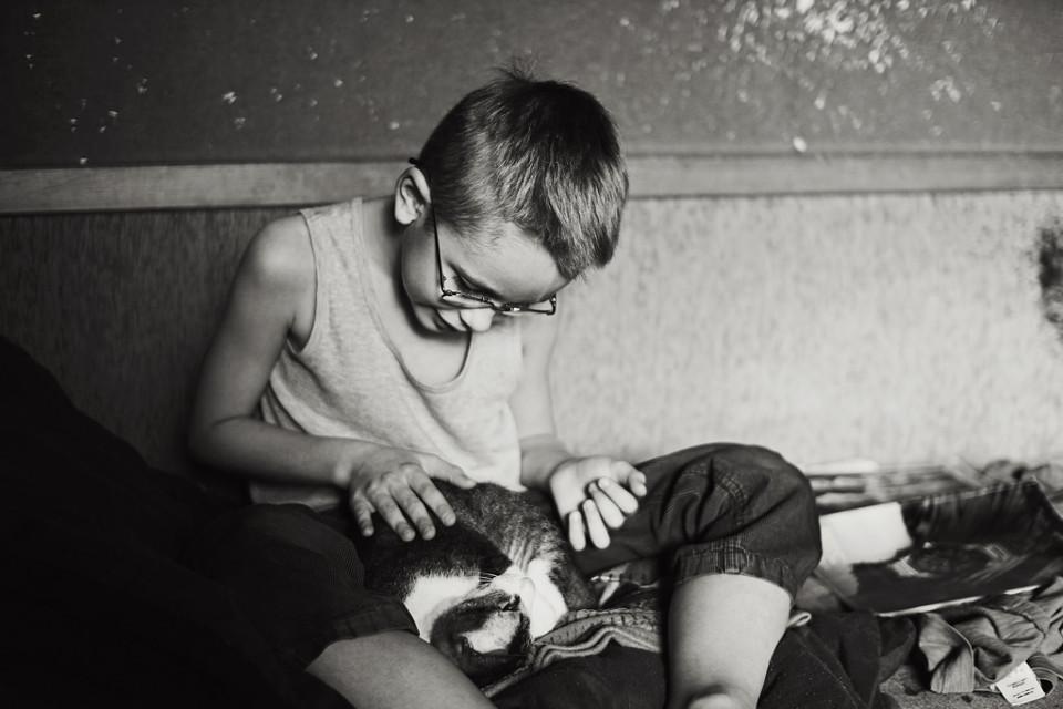 Schwarzweißfoto eines Jungen, wie er mit einer Katze spielt.