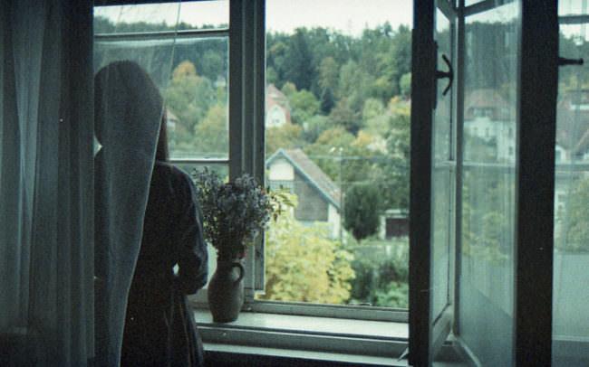Eine Frau steht am Fenster und schaut hinaus.