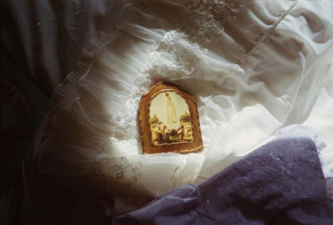 Ein christliches Symbolbild liegt auf einem weißen Kleid.