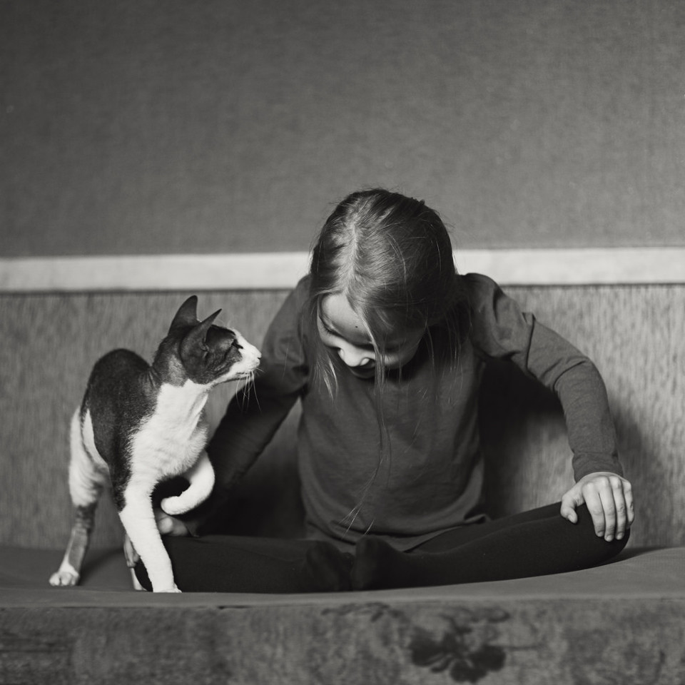 Schwarzweißfoto eines Mädchen und einer Katze, wie sie sich anschauen.