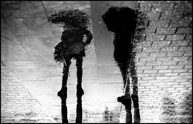 Schwarzweißaufnahme eines Spiegelung von Personen in einen Pfütze.