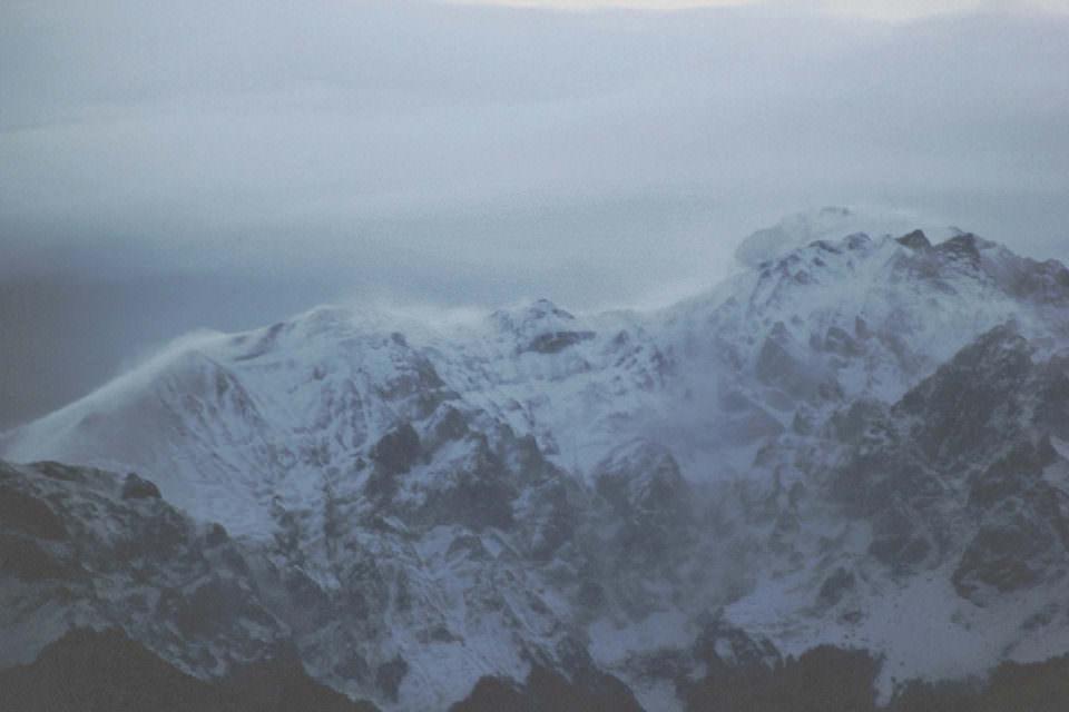 Wolken über schneebedeckten Bergen.