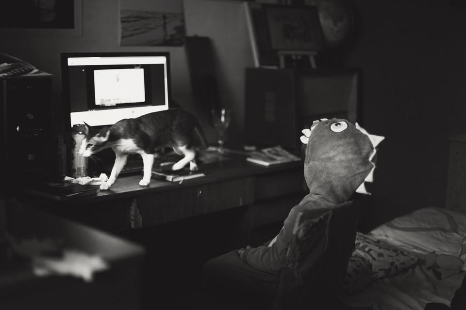 Schwarzweißfoto eines verkleideten Kindes vor einem Computer.