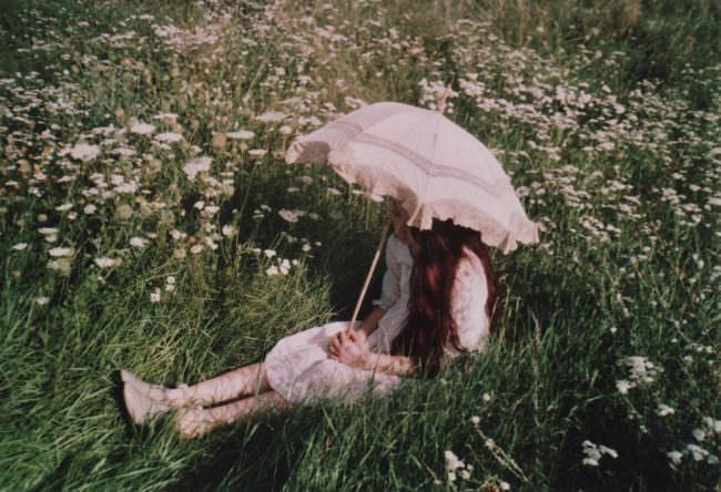 Eine Frau mit Schirm sitzt auf dem Boden.