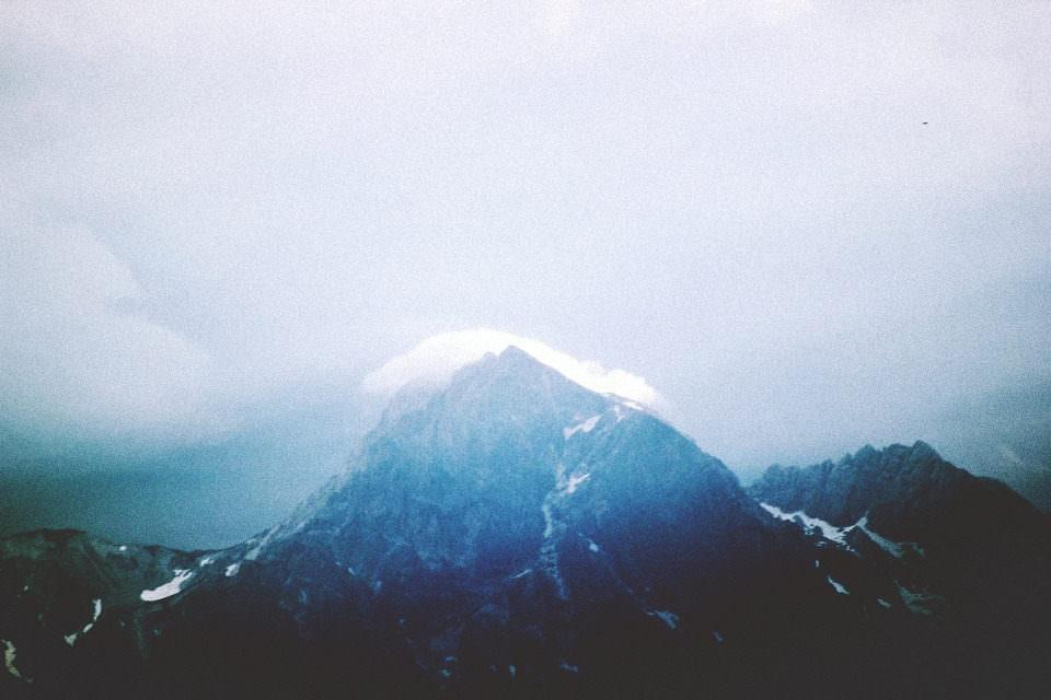 Wolkenformationen am Himmel über einem Berg.