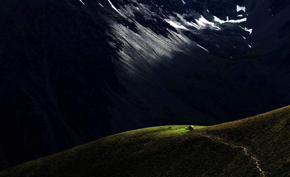 Kleine Hütte auf einem Berg vor einer Felswand.