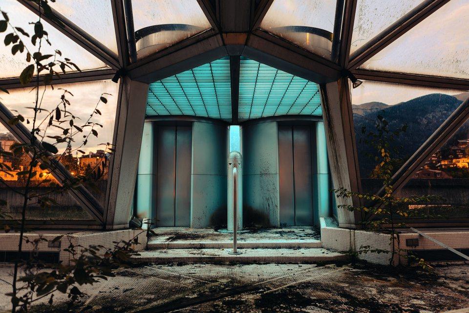 Surreale Architekturaufnahme zweier Aufzüge in einem alten Gewächshaus.