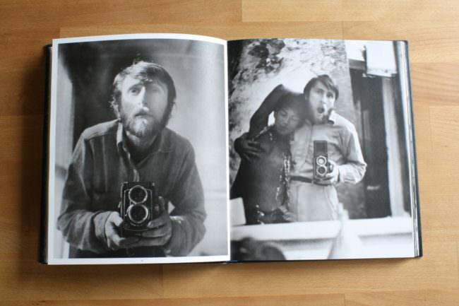 Schwarzweißfoto von einem Mann mit Kamera in einem Buch.