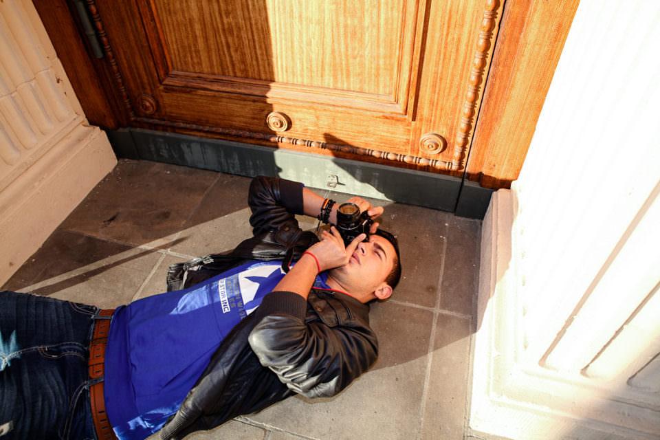 Eine Person liegt am Boden und fotografiert nach oben