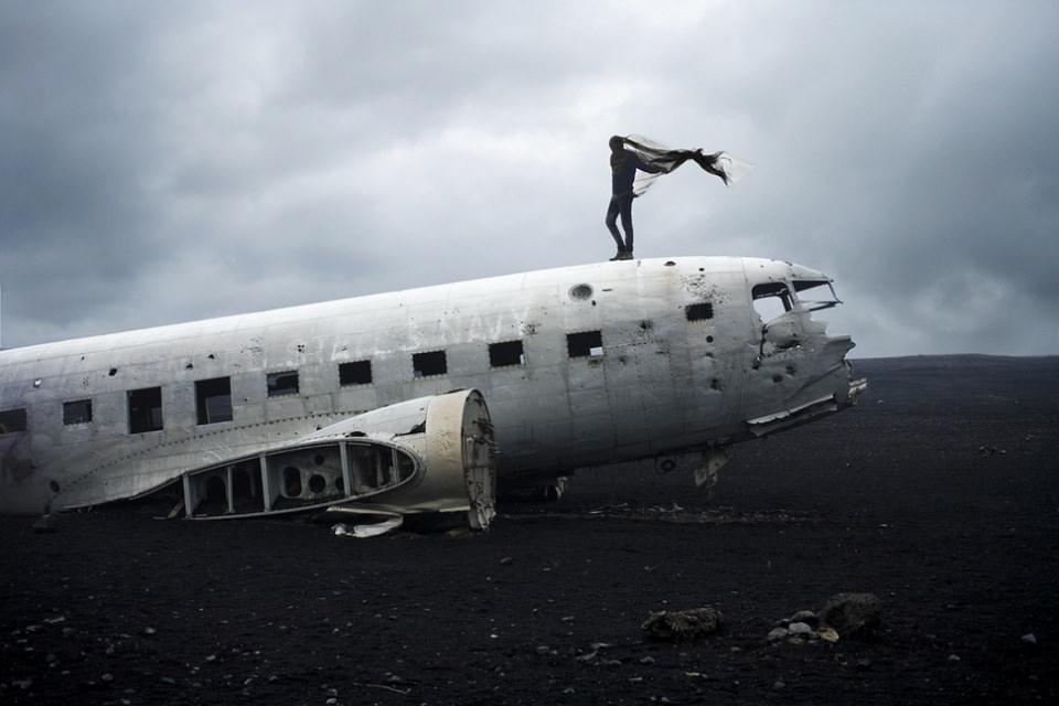 Ein Mensch mit wehendem Umhang steht auf einem Flugzeugwrack.