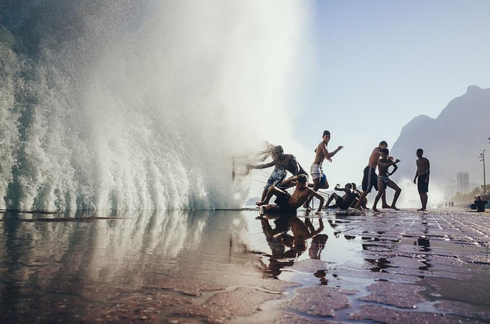 Eine Gruppe Menschen springt auf einem Platz zwischen Wasserfontänen herum.